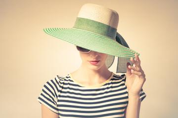 In studio fashion portrait of woman wearing hat.