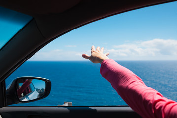 Road trip. Woman in her car enjoying the ocean breeze trough her finger tips