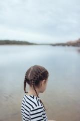 petite fille avec des tresses dans l'eau