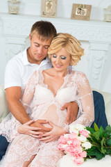 Happy future father with beautiful cute pregnant woman sitting on sofa with flowers.
