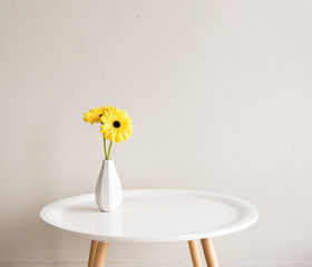 Yellow gerberas in small white vase on round table against neutral background