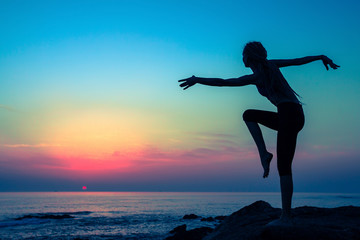 Silhouette of young flexible dancing woman on the sea coast during twilight.