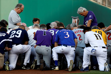 Father Pat Conroy, Chaplain of the House of Representatives, leads members of the Republican and Democratic Congressional baseball teams in prayer prior to the Congressional Baseball Game at Nationals Park in Washington