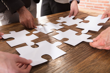Businesspeople Arranging The Puzzle