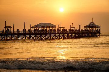 Sunset at pier of Huanchaco town, Peru