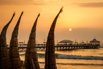 The sunset with traditional boat craft at Huanchaco town, Peru