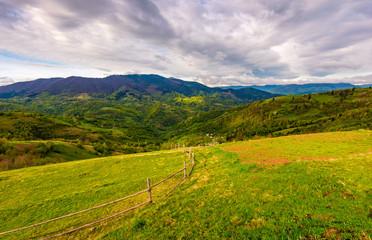 wooden fence through rural field on hillside