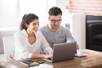 Happy Couple Looking At Laptop On Table