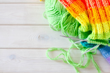 Closeup of basket with colorful yarn clews. Knitted Socks.
