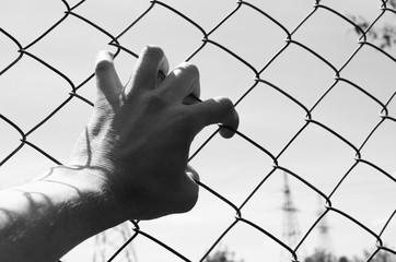 Refugee hand on fence. Refugee concept.Dark tone. Vintage.