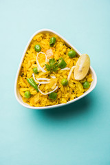 Indian Breakfast Dish Poha Also Know as Pohe or Aalu poha made up of Beaten Rice or Flattened Rice. The rice flakes are lightly fried in oil with mustard, chilly, onion, curry leaves and turmeric
