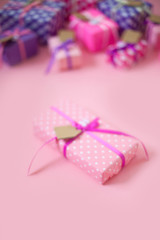 Colored gift boxes with colorful ribbons. Pink background. Gifts for St. Valentine's Day or a birthday.