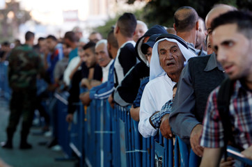 Palestinians wait at an Israeli checkpoint as they make their way to attend Friday prayer of the holy fasting month of Ramadan in Jerusalem's al-Aqsa mosque, in Bethlehem