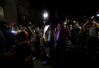 A couple wearing Batman costumes watches as a bat-signal is projected on City Hall in honor of late actor Adam West in Los Angeles