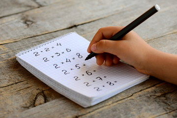Child solves mathematics examples. Child holds a black marker in his hand. Notebook sheet with multiplication table examples. Studying a multiplication table concept