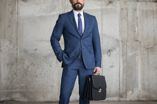 Cropped shot of confident businessman in formal wear holding briefcase while standing with hand in pocket