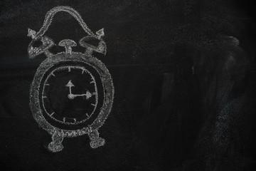 School alarm clock drawn with chalk on blackboard and copyspace