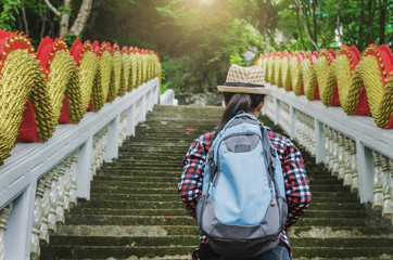 Young beauty woman traveler with backpack and hat walking staircase  temple background