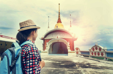 Young woman traveler with backpack and hat looking  temple background