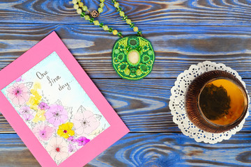 """Ceramic bowl piala cup with green tea with jasmine and picture card with inscription """"One fine day"""", green pendant made from a seed bead on blue boards background. Top view. Happiness Still life"""