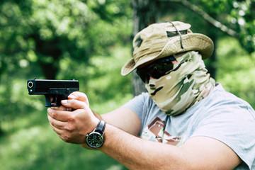 A man shoots a pistol. He looks at us