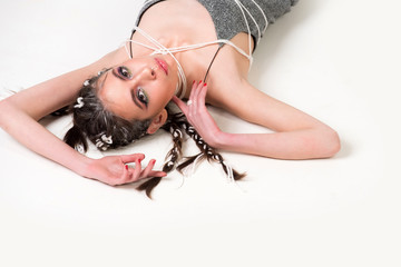 woman with stylish braids and makeup lying on floor