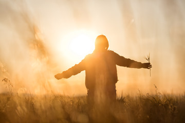 Middle aged caucasian woman standing in the sunlit field with open arms, embracing nature