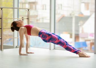 Young woman practicing yoga near big window