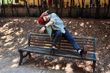 Ragazza hipster balla danza moderna sulla panchina nel parco