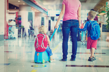 mother and two kids walking in airport