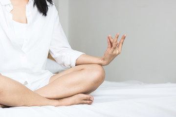 Asian women play yoga on bed in morning