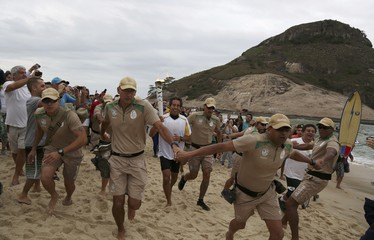Brazilian surfer Rico de Souza carries the Olympic torch after surfing with it at praia da Macumba (Macumba beach) in Rio de Janeiro, Brazil
