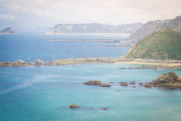 Amazing landscape with ocean, cliffs, beach, greens and flowers in summer day; wallpaper of the Bay of Biscay, Cantabrian Sea