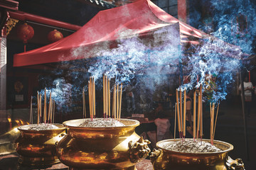 Incense sticks burning at the pots in chinese temple