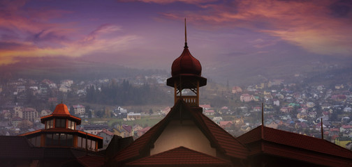 Old city at sunset . Ukraine. Downtown of Skhodnits. Architectural monument . red rooftops . fog in mountains . Wonderful little village