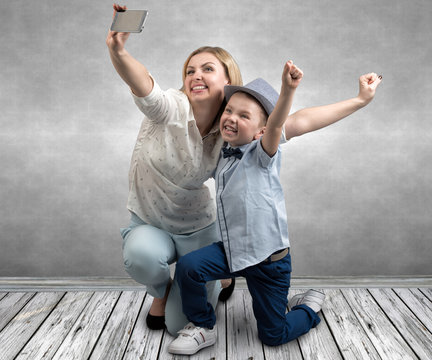 Young mother and son are photographed on a mobile phone ,making selfie .Stylish,trendy,modern