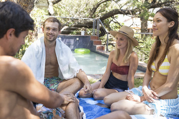 Group of friends relaxing in garden at the poolside