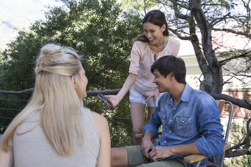 Smiling woman showing cell phone to friends on veranda