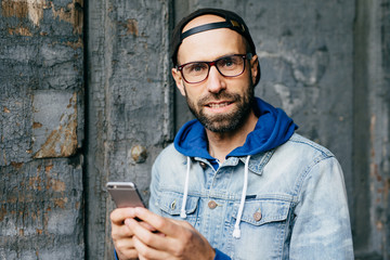 Close-up portrait of bearded blue-eyed man in stylish cap and denim anorak holding mobile phone surfing the Internet cheking his emails and communicating with friends. Technology and communication