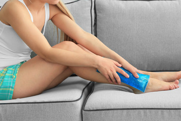 Young woman applying cold compress to leg at home