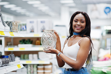 Gorgeous african american woman holding a silver vase in the shop.