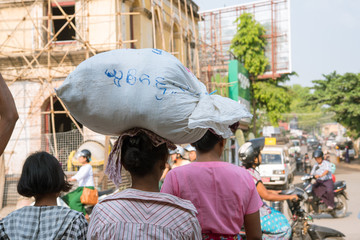Burmese woman carrying bag on her head, Bagan, Myanmar