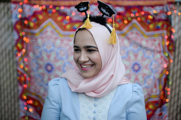 Dina Sayedahmed smiles as she stands in front of a makeshift photo booth in her family's backyard ahead of a graduation celebration and Iftar feast during Ramadan in Bayonne