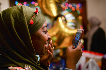 Halima Mahuoud, a Togolese Ghanaian American Muslim, smiles as she photographs her Egyptian American Muslim friend cutting cake at her graduation celebration and Iftar feast during Ramadan in Bayonne