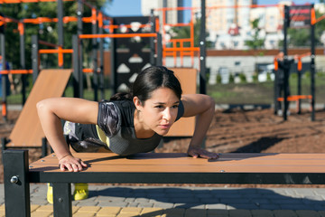 Young woman doing push up exercise at the spots ground.