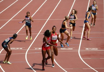 Phyllis Francis of the U.S. (C) passes the baton to her teammate Jessica Beard in the women's 4 x 400 metres relay heat during the 15th IAAF World Championships at the National Stadium in Beijing