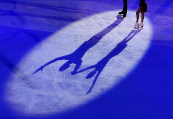 Gold medal winners Volosozhar and Trankov of Russia cast shadows during the awards ceremony after the pairs free program at the ISU European Figure Skating Championship in Bratislava