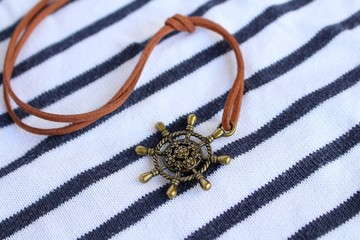 un pendentif barre de bateau en cuivre monté sur un lacet de cuir sur fond marin