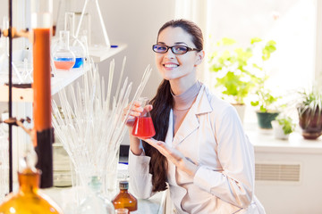 Woman scientist in laboratory with beaker posing