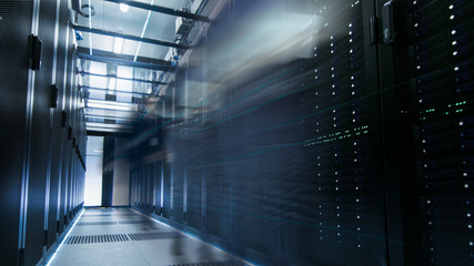 Shot of a Working Data Center With Rows of Rack Servers. People Walk and Work there, they are Blurred in Motion. Long Exposure Shot.